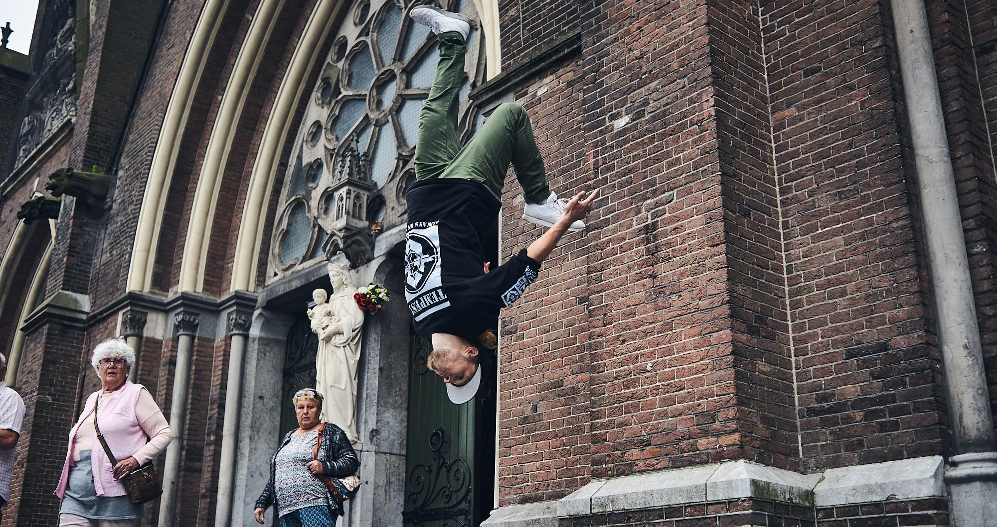 Bart van der Linden performing a freerunning trick on a church in Eindhoven