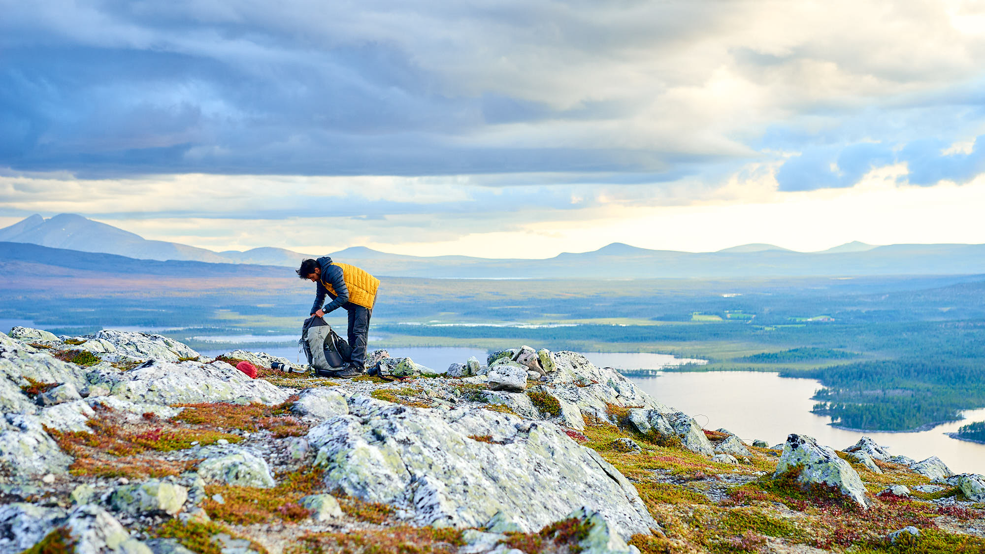 Hiker packing his bag on a mountaintop in Norway
