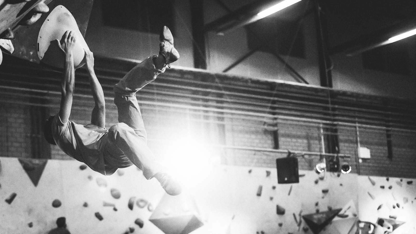 Climber making a huge swing in a climbing move in a bouldergym