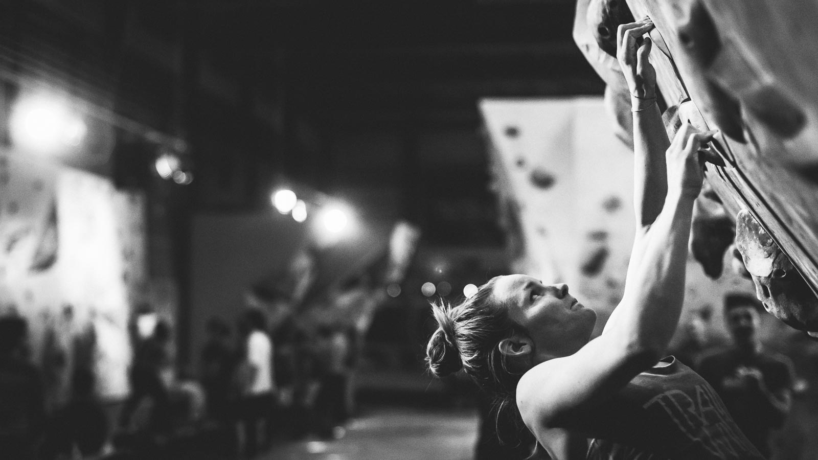 Female climber focused on a hold in an indoor boulder gym