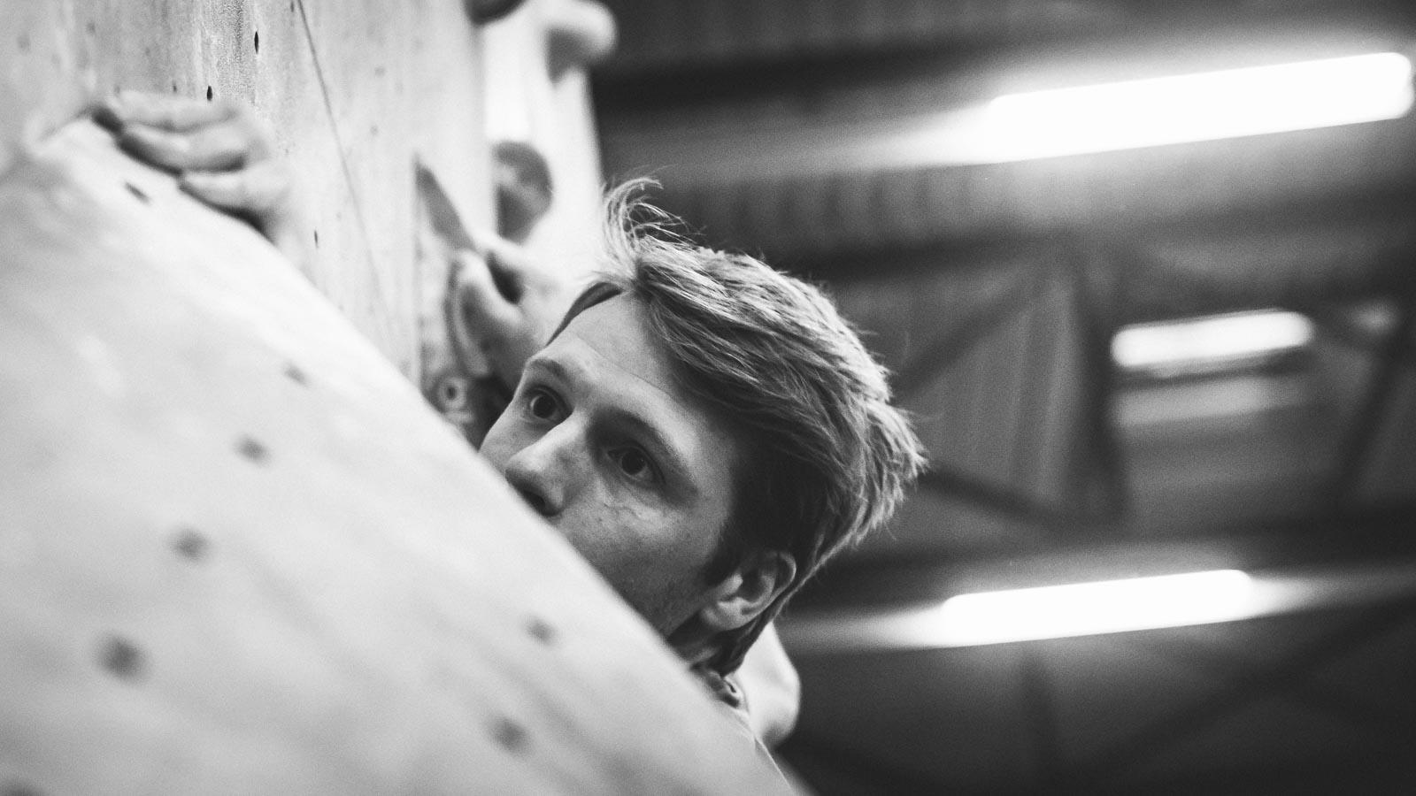 Focus on a climber's face while climbing in a bouldergym