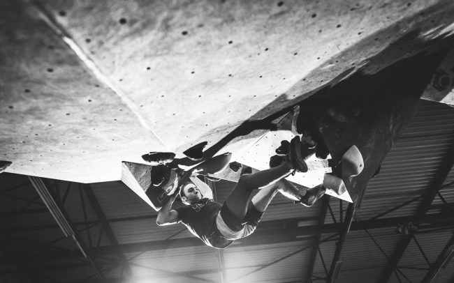 Climber climbing in a roof in an indoor bouldergym