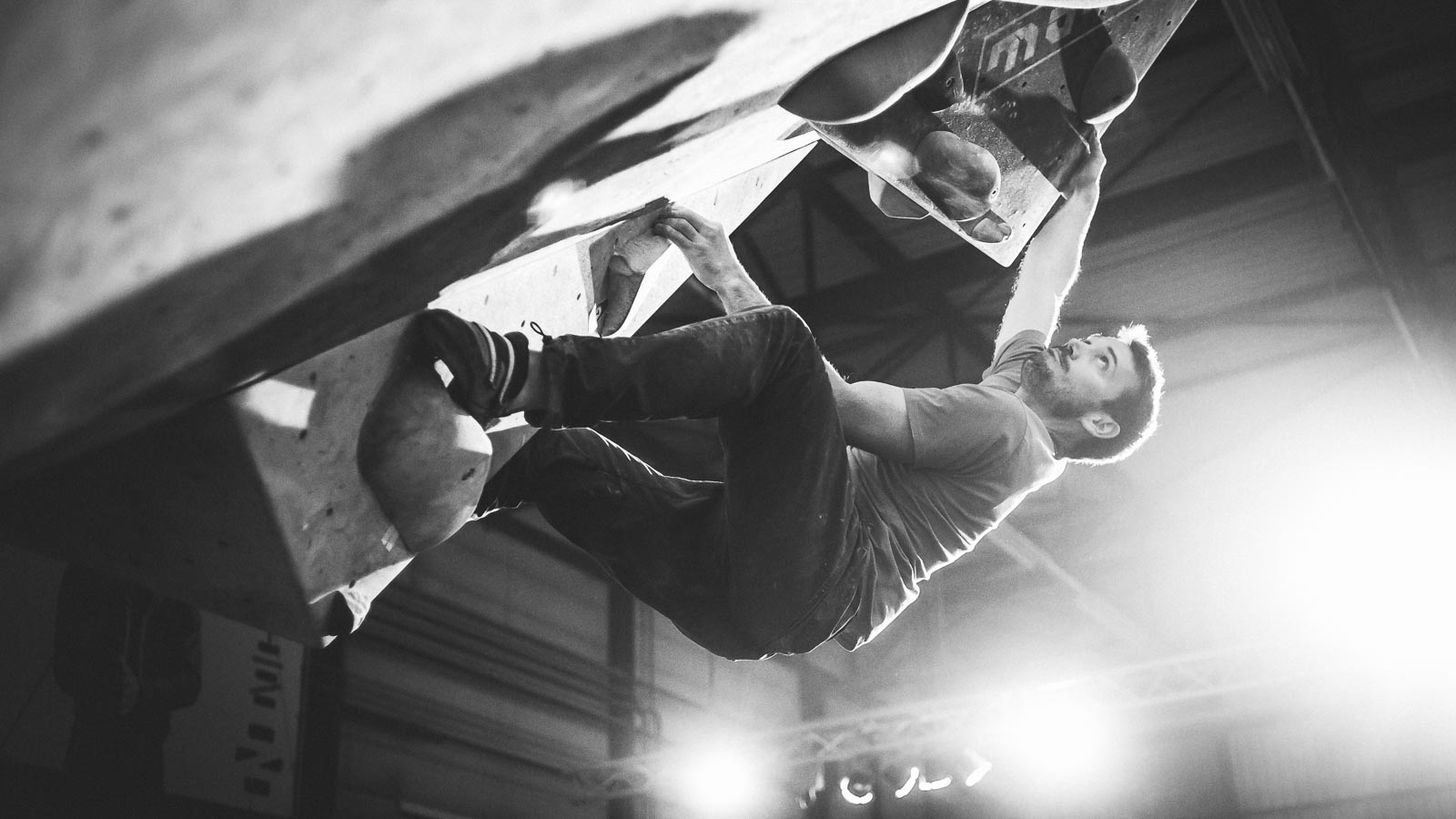 Climber hanging from holds in an indoor steep climbing wall