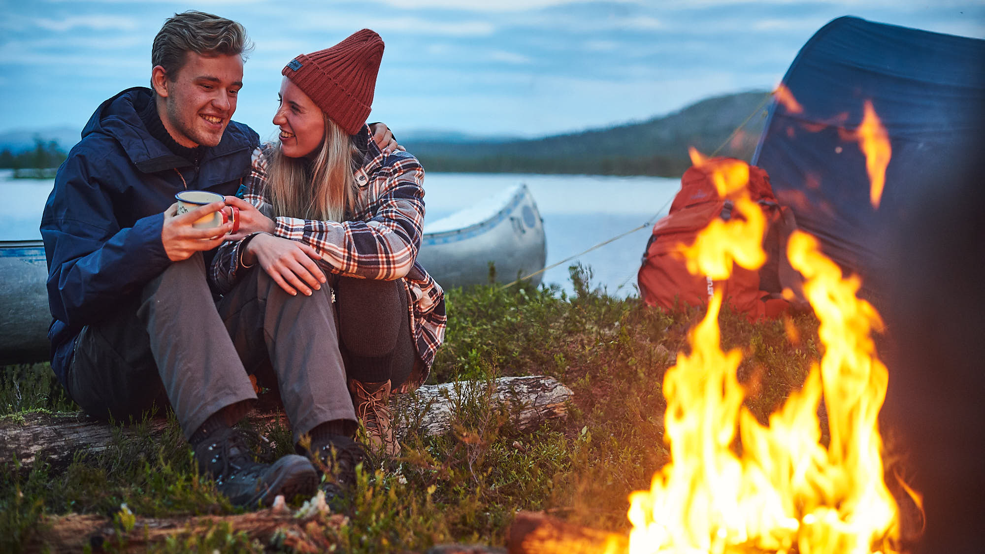 Couple sitting by a campfire with their canoe in Norway