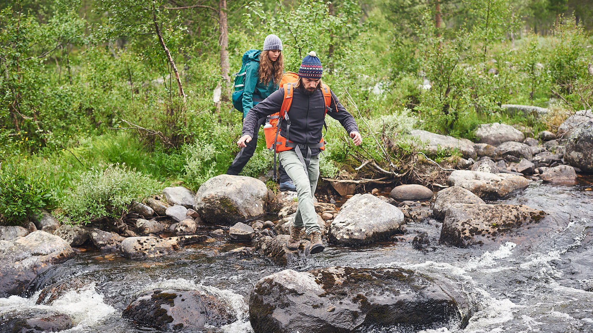 Hikers crossing a wild river in Norway
