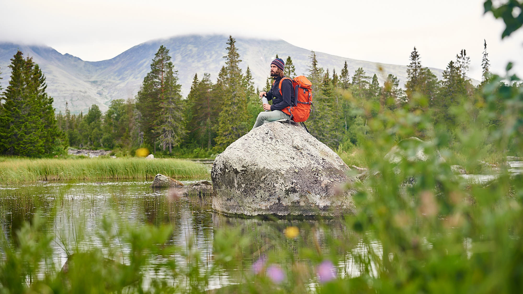Hiker in the wild sitting on a rock in Norway
