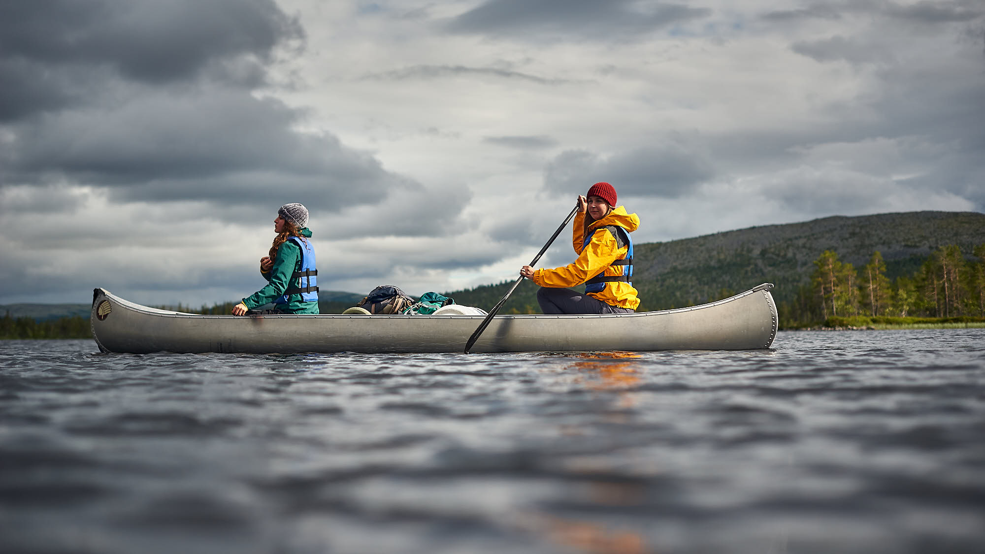 Low angle view of two girls in a canoe on a lake in Norway