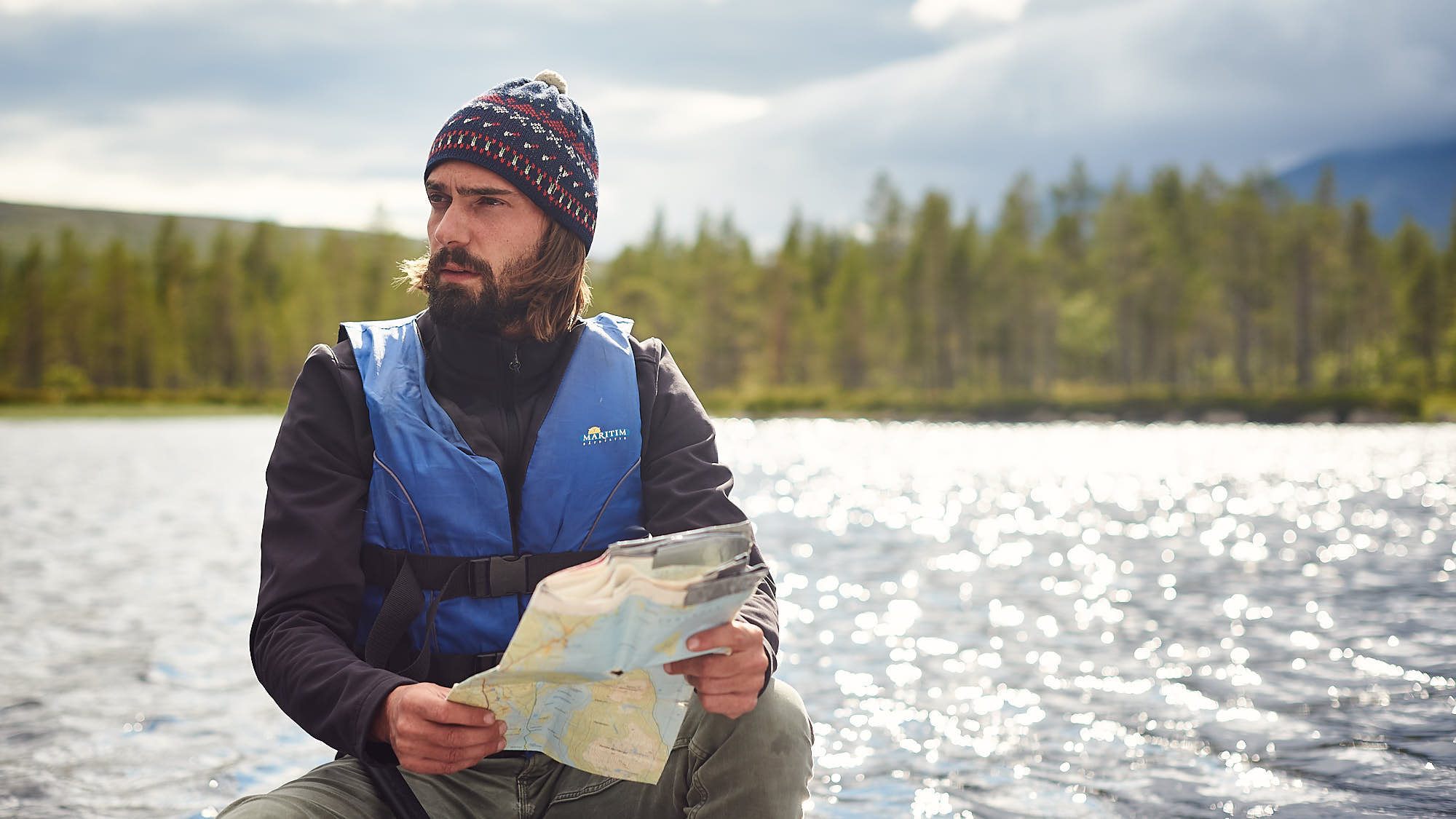 Bearded man reading a map in a canoe on a lake in Norway