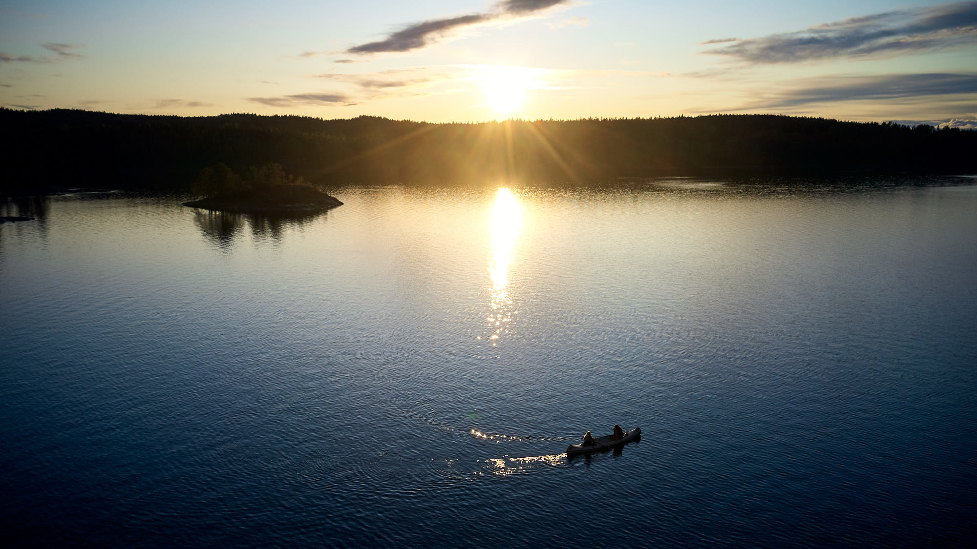 Canoe with two travellers at sunset on a lake in Sweden