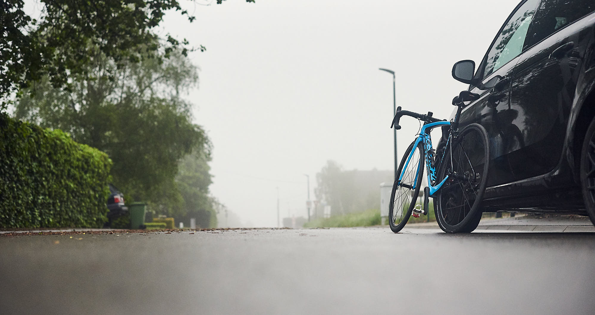 Road racing bike leaning against a car on a foggy morning