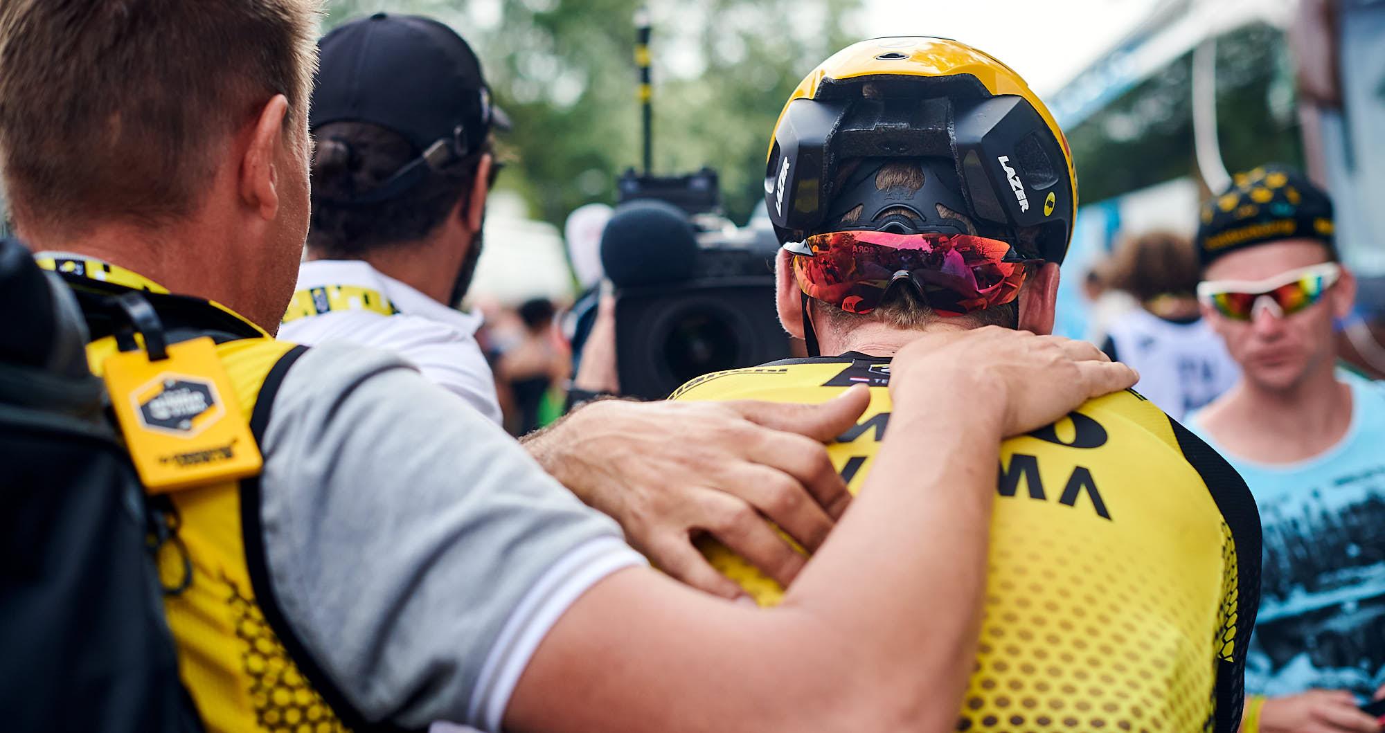 Soigneur leading Mike Teunissen to the Tour de France podium