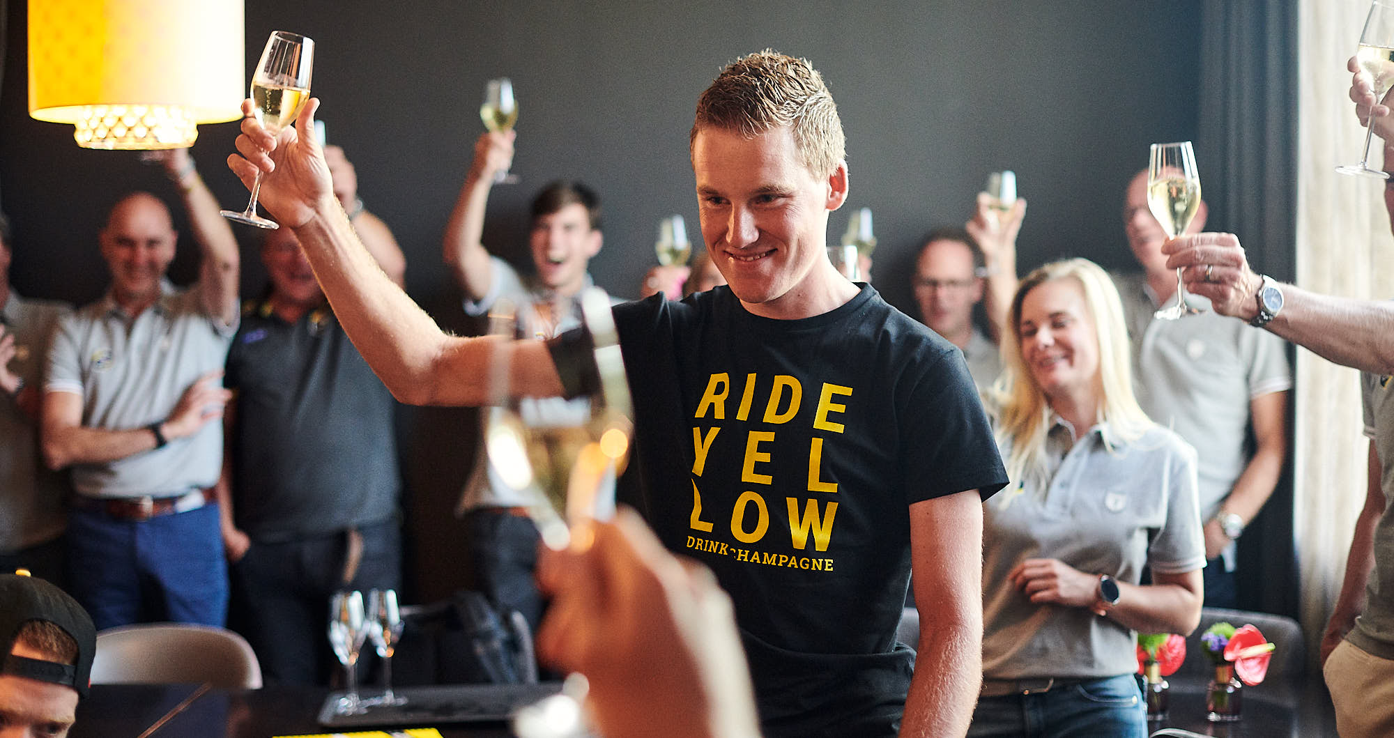 Mike Teunissen raising a glass of champagne after taking the yellow jersey in the Tour de France