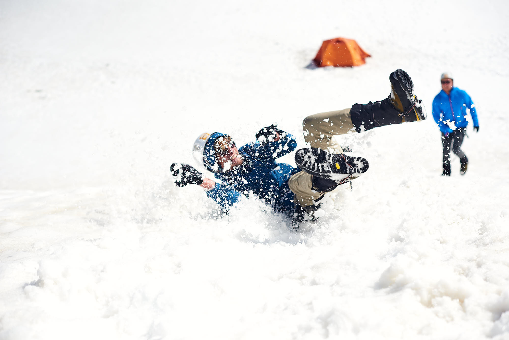 Alpinist doing a training drill, sliding down a hill, trying to stop his fall with an ice axe
