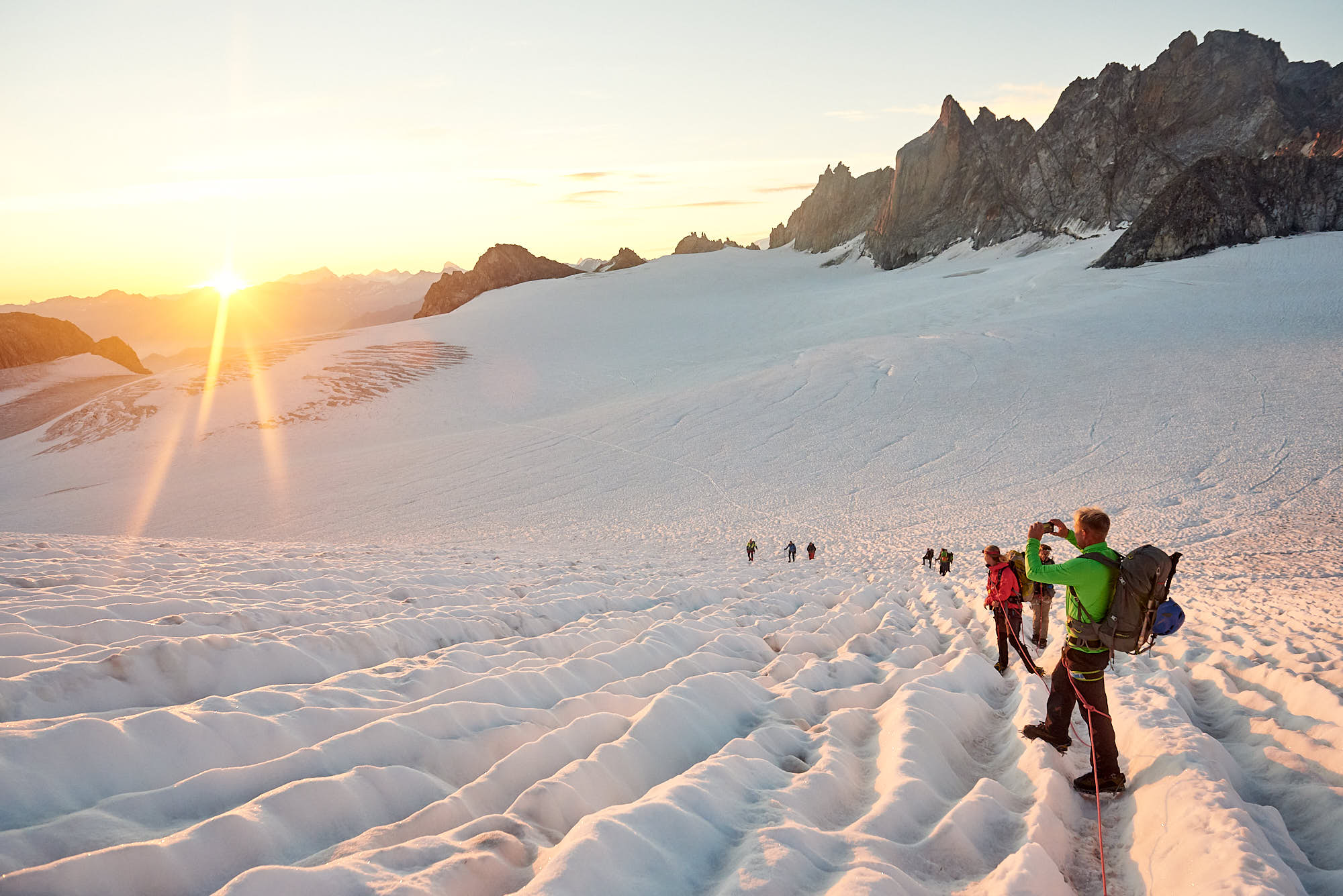 Alpinists enjoying a sunrise high in the Swiss Alps