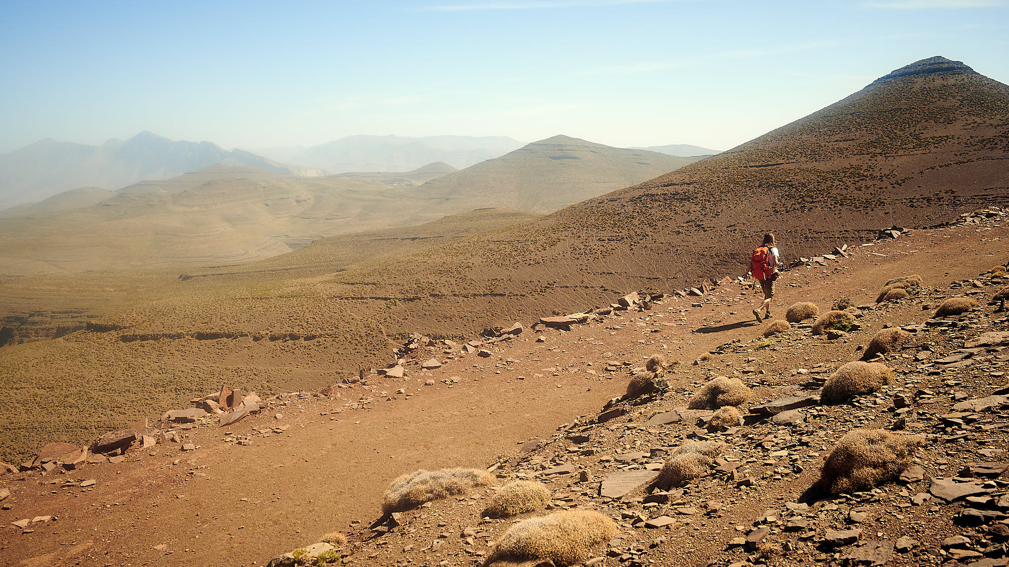Hiker on a trail in Morocco's High Atlas mountain ridge