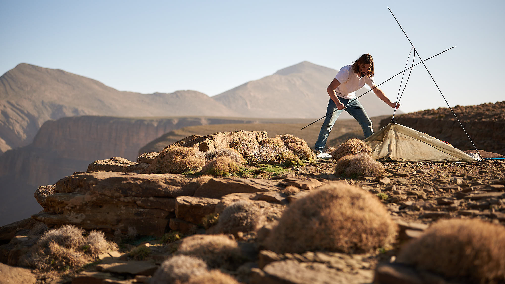 Hiker pitching a tent in Morocco's High Atlas mountain ridge