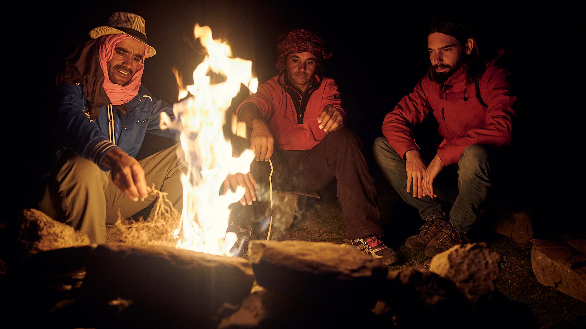 Berber guides and tourist sit by a campfire in Morocco's High Atlas