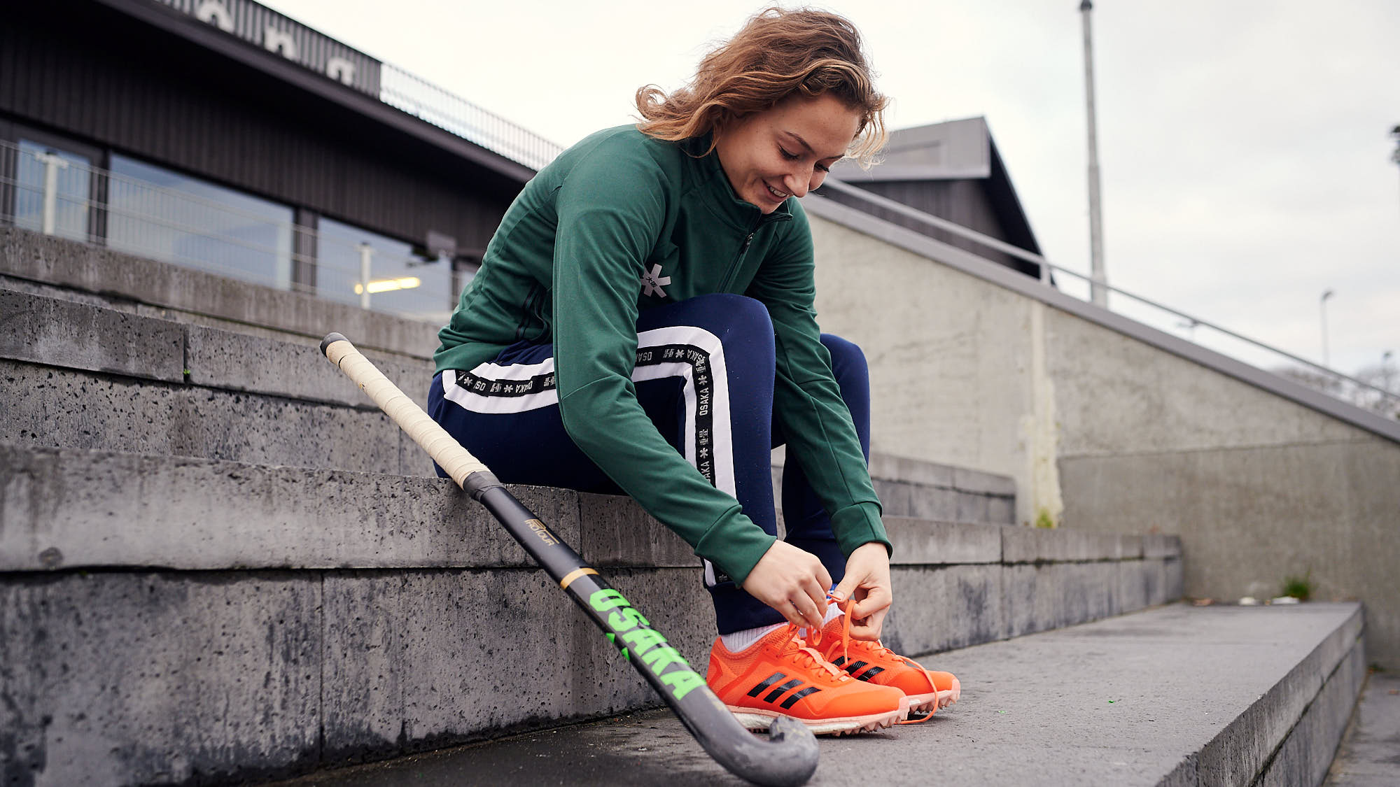 Marijn Veen tying her shoelaces by the side of the hockey pitch